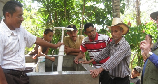 Farmers of El Cablotal take a keen interest in the flex-pump that can shoot water a far distance. Pastor Rios (holding the pump) plans to take what he is learning to his church members.
