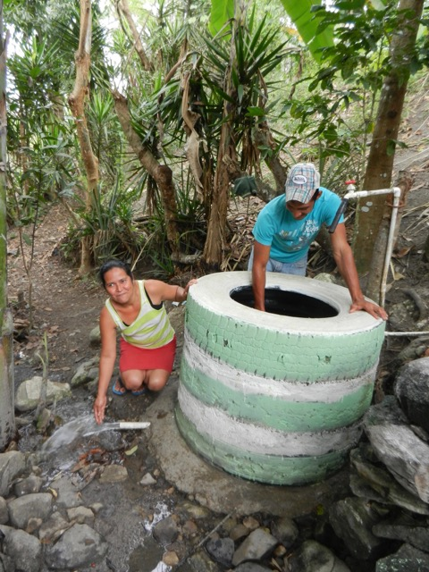 The new owner of a new water-conserving sink shows where the filtered water drains out of the bottom and into her garden.