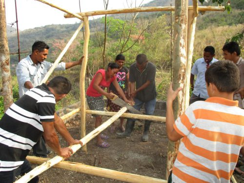 Anibal Rios (shown on left), a farmer from El Cablotal, is showing farmers in El Puente how to build a chicken coop.  Predators kill the hens and eggs if left unprotected overnight.