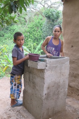 Used to carrying all the kitchen water for family use uphill, Altagracias Peña is grateful for this water-conserving sink which filters the wastewater and drains it into a new nearby garden.
