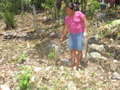 A new participant, Maria Vasquez provides crip irrigation to her cacao seedling using a plastic bottle with pin holes in the cap.