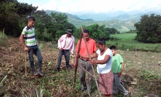 A woman farmer learns to use the A-frame tool to plant corn seeds across the mountainside contour. This is often the first new agricultural practice that participants want to adopt.