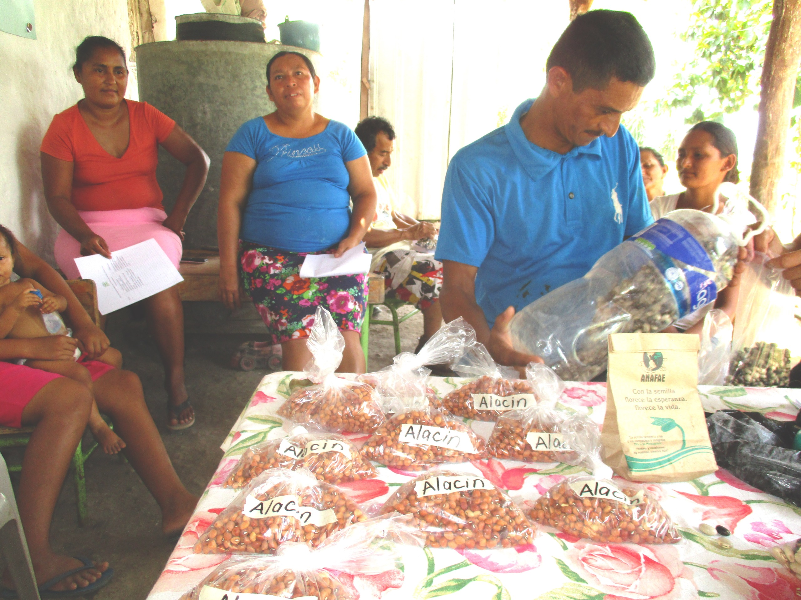 Vidal Chavez, husband of Mercedes Rios, explaining to women how to save seeds in a plastic bottle.